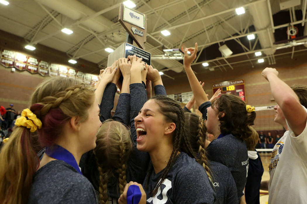 Boulder City teammates hold up their trophy as they celebrate their 3-2 win over Moapa Valley during the class 3A state volleyball championship at Faith Lutheran in Las Vegas on Saturday, Nov. 11, ...