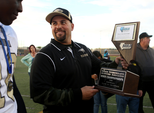 Spring Mountain's Head Coach Aaron Masden holds his team's trophy after winning the class 1A state football final neutral playoff game against Pahranagat Valley at Clark High School in Las Vegas,  ...