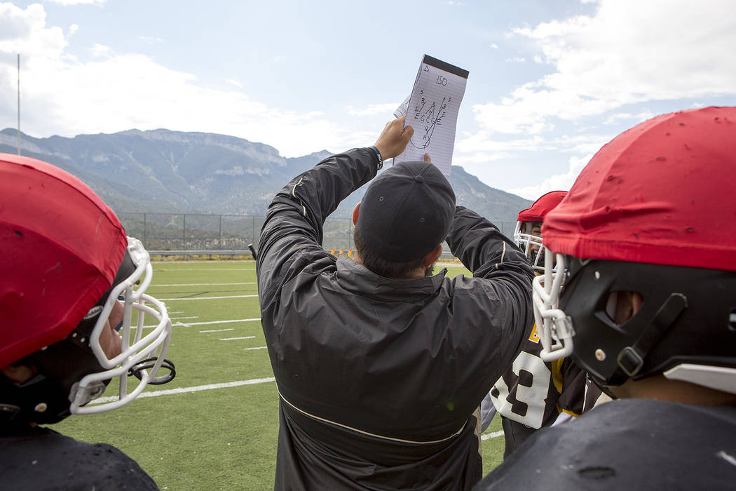 Head coach Aaron Masden goes over a play with players at Spring Mountain Youth Camp on Tuesday, Aug. 29, 2017. Bridget Bennett Las Vegas Review-Journal @bridgetkbennett