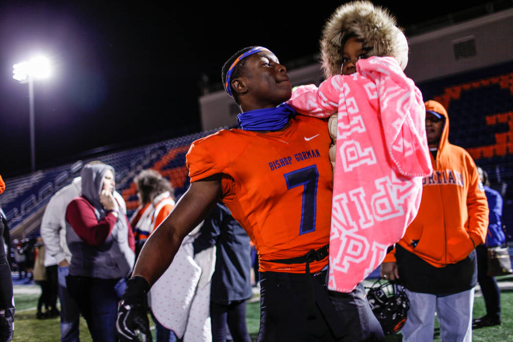 Bishop Gorman's Jordan Lee (7) holds Carter Stephens, 5, as he celebrates a 42-7 victory against Arbor View in the Class 4A Sunset Region Title football game at Bishop Gorman High School in Las Ve ...