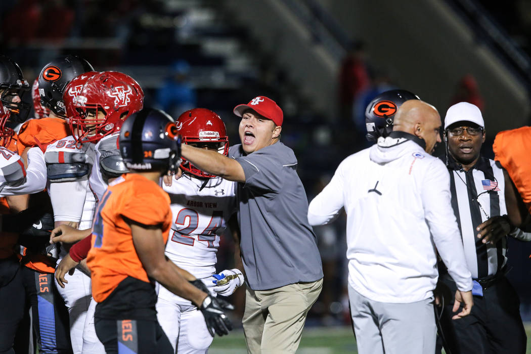 An Arbor View staffer helps break up a minor fight between Arbor View and Bishop Gorman during the fourth quarter of the Class 4A Sunset Region Title football game at Bishop Gorman High School in  ...
