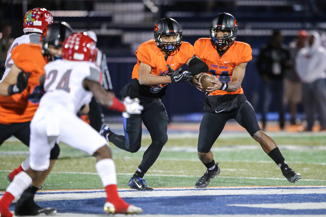 Bishop Gorman's Dorian Thompson-Robinson (14), right, fakes a handoff to teammate Amod Cianelli (28), left, during the first quarter of the Class 4A Sunset Region Title football game against Arbor ...