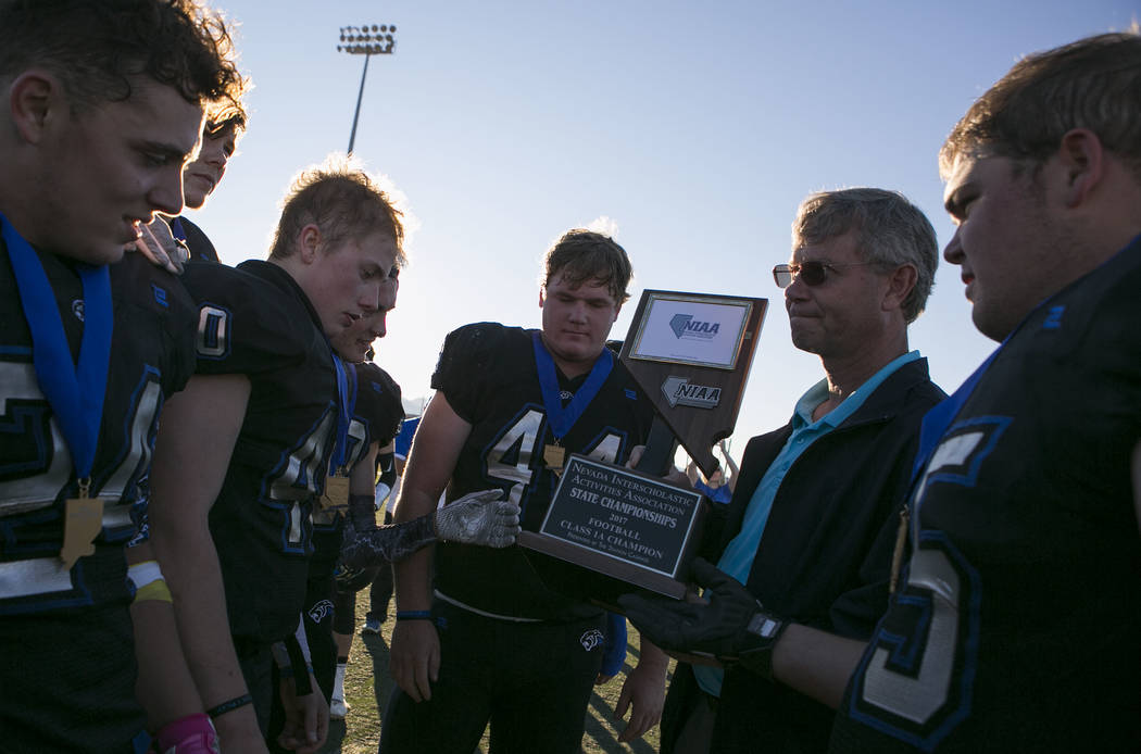 Pahranagat Valley players are presented with their class A state championship trophy after their 68-18 win over Spring Mountain at Indian Springs High School in Indian Springs, Saturday, Nov. 18,  ...