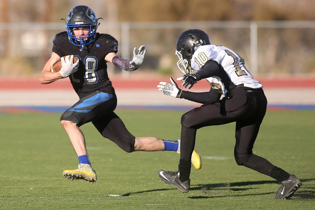 Pahranagat Valley player Hunter Hollingshead (28) tries to avoid Corvell Fisher (10) during the class A state championship game against at Indian Springs High School in Indian Springs, Saturday, N ...