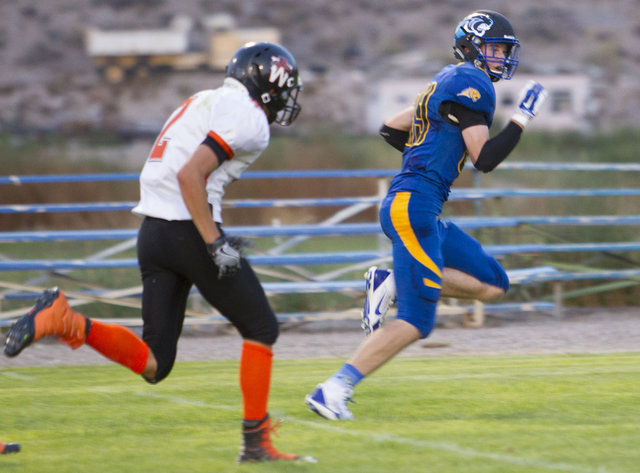 Pahranagat Valley Panthers tight end Culen Highbe, right, runs the ball for a touchdown against Wells, Nevada players during the season opening eight-man high school football game in Alamo, Nevada ...