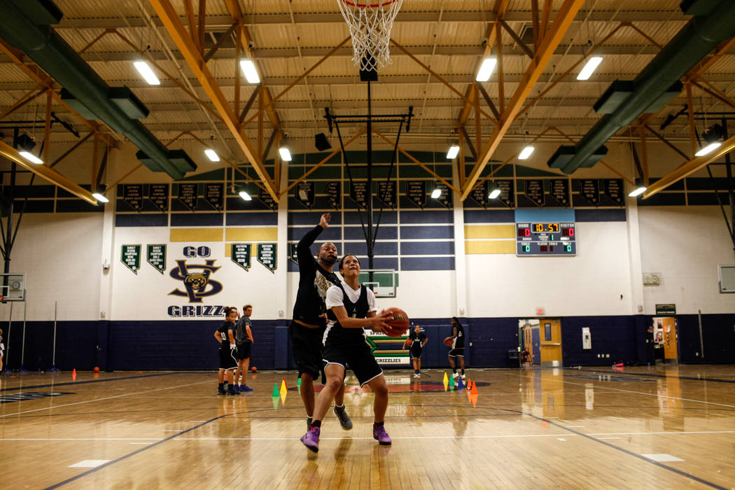 Essence Booker (3) goes for a shot as assistant coach Errol Campbell guards her during a basketball practice at Spring Valley High School in Las Vegas, Thursday, Nov. 16, 2017. Joel Angel Juarez L ...