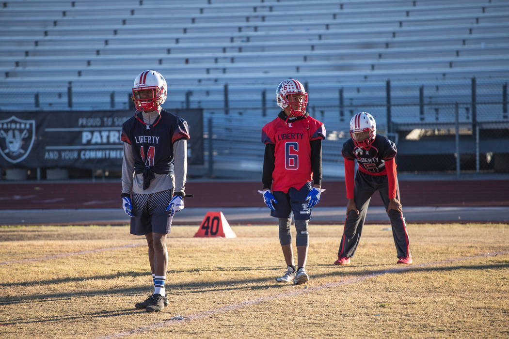 Liberty Patriots' Allan Mwata, left, Cervontes White (6), center, and Davion Ware (5), line up in a formation during a football practice at Liberty High School in Henderson, Thursday, Nov. 23, 201 ...