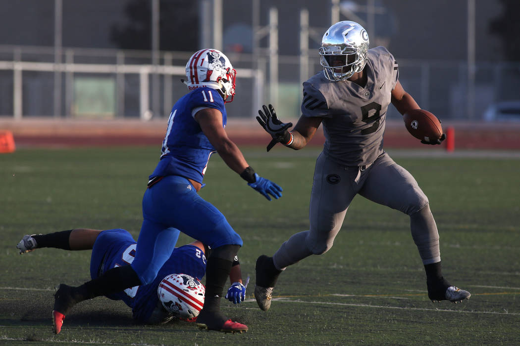 Liberty player Jake Dedeaux (11) takes after Bishop Gorman player Brevin Jordan (9) as he runs the ball during the class 4A state semifinal football game at Rancho High School in Las Vegas, Friday ...
