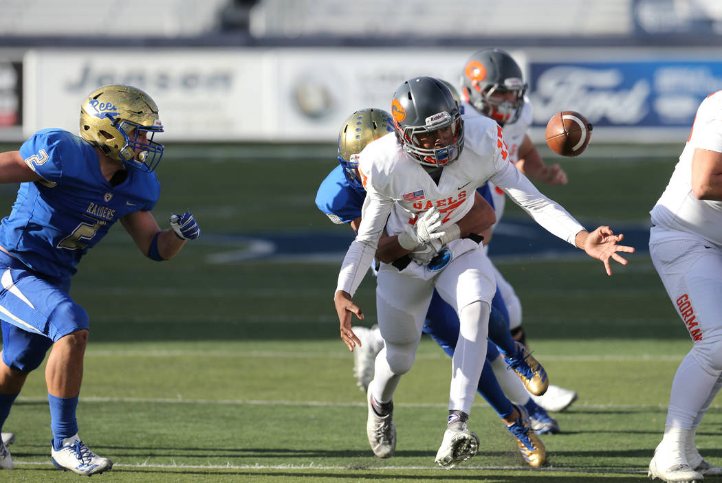 An unidentified Reed defender knocks the ball loose from the hands of Bishop Gorman's Issac Alcaraz in the second half of the NIAA 4A state championship football game in Reno, Nev., on Satu ...