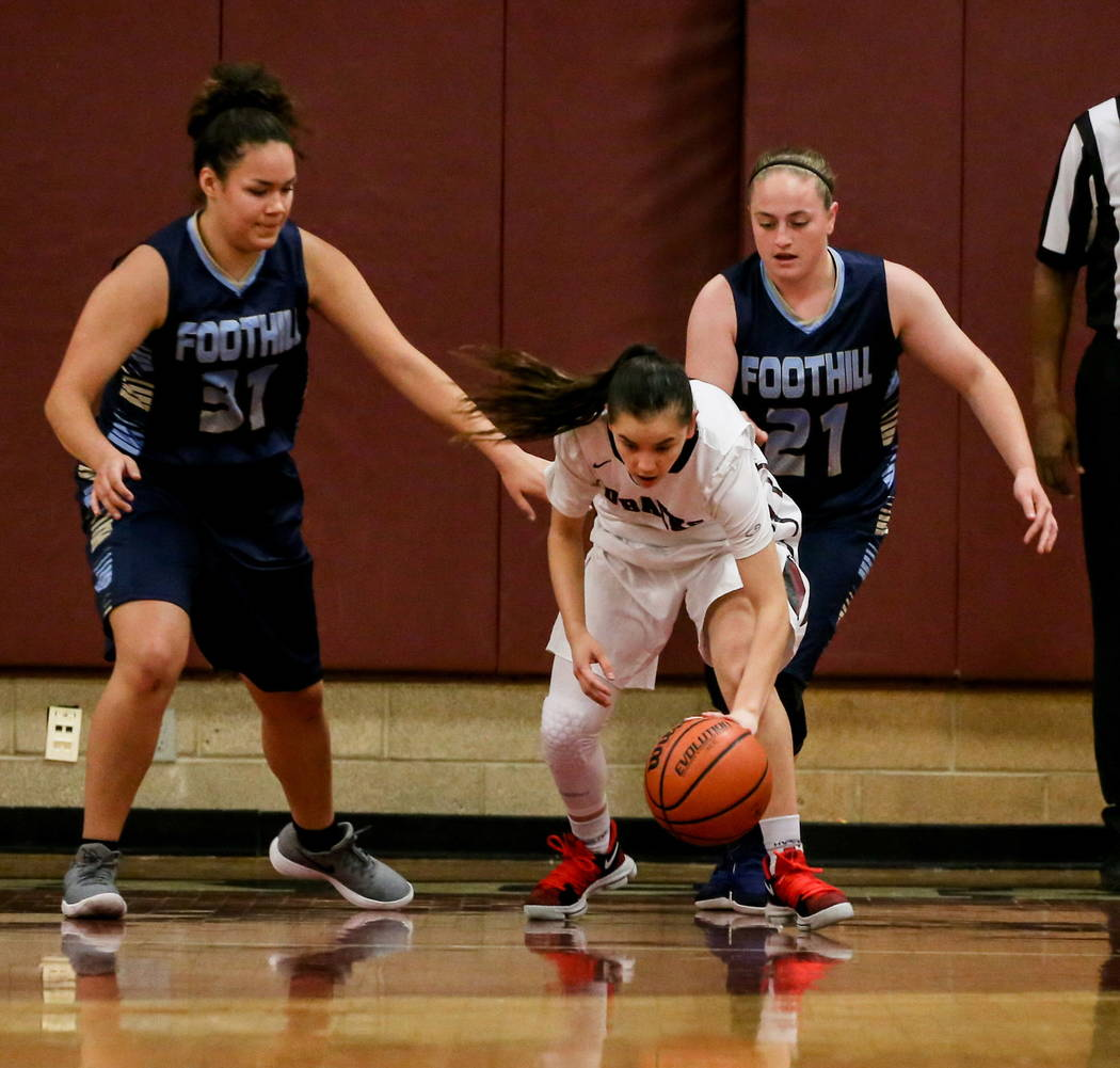 Desert Oasis' Brianna Clark (4), center, dribbles the ball as she is guarded by Foothill's Bri Rosales (31), left, and Rhianna Cox (21), right, during the first quarter of a basketball game at Des ...