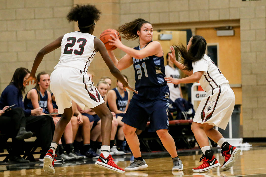 Foothill's Bri Rosales (31), center, is guarded by Desert Oasis' Desi-rae Young (23), left, and Kalena Halunajan (11), right, during the first quarter of a basketball game at Desert Oasis High Sch ...