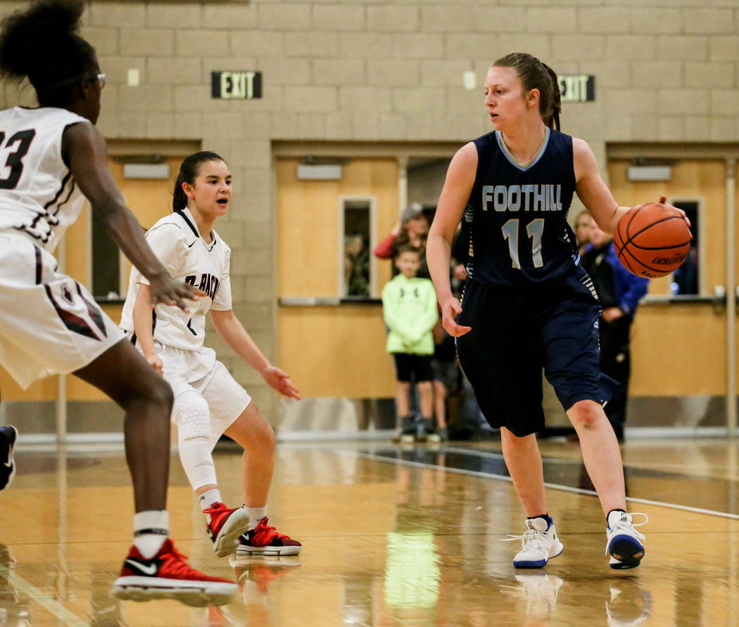 Foothill's Kaylee Hall (11), right, dribbles the ball as she is guarded by Desert Oasis' Desi-rae Young (23), left, and Brianna Clark (4), center, during the first quarter of a basketball game at  ...