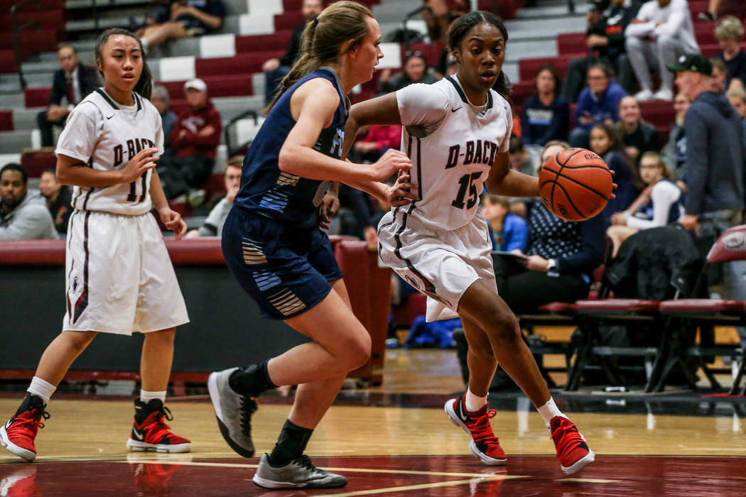 Desert Oasis' Ahmaya Smith (15), right, dribbles the ball as she is guarded by Foothill's Aqui Williams (2), center, during the second quarter of a basketball game at Desert Oasis High School in L ...