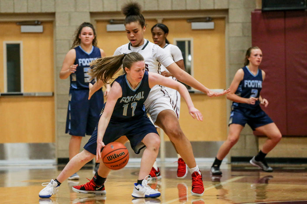 Foothill's Kaylee Hall (11), left, dribbles the ball as she is guarded by Desert Oasis' Dajaah Lightfoot (35), right, during the third quarter of a basketball game at Desert Oasis High School in L ...