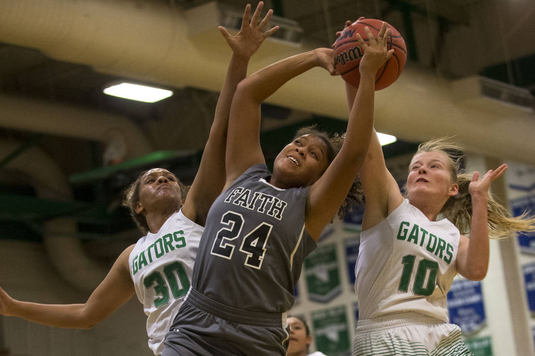 Faith Lutheran's Kayla Proctor (24) is blocked by Green Valley's Analiz Ceja (30) and Jordan Rood (10) during a junior varsity basketball game at Green Valley High School in Henderson on Tuesday,  ...
