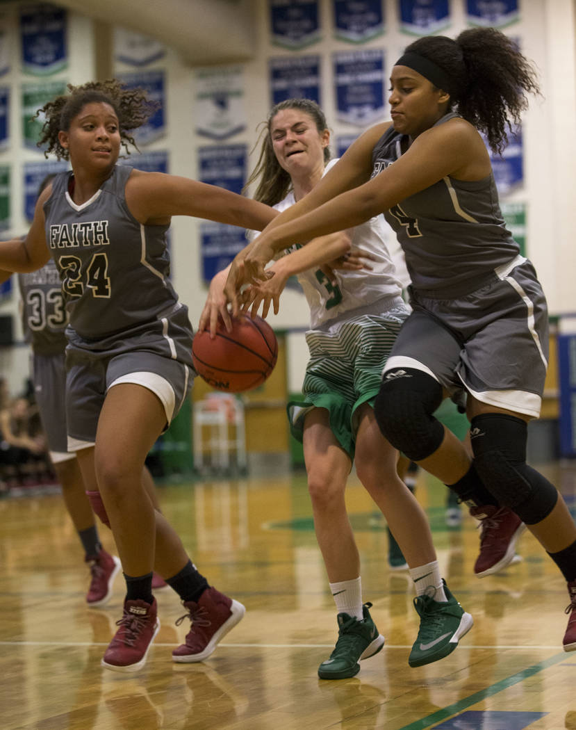 Faith Lutheran's Kayla Proctor (24) and Casey Proctor (4) rip the ball away from Green Valley's Alexis Mensah (3) during a junior varsity basketball game at Green Valley High School in Henderson o ...
