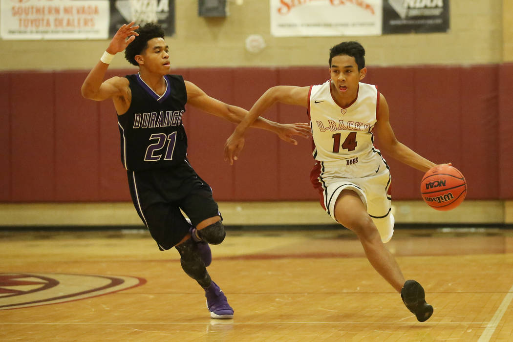 Durango player Anthony Hunter (21) trails after Desert Oasis player Nate Van (14) as he drives the ball up the court during a game at Desert Oasis High School in Las Vegas, Wednesday, Dec. 6, 2017 ...