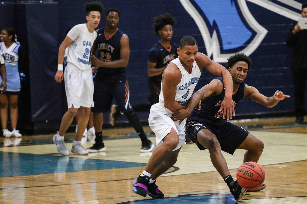 Canyon SpringsՠKevin Legardy (4), left, and Legacyճ Cristian Pitts (3), right, race toward the ball during the first quarter of a basketball game at Canyon Springs High School in North ...