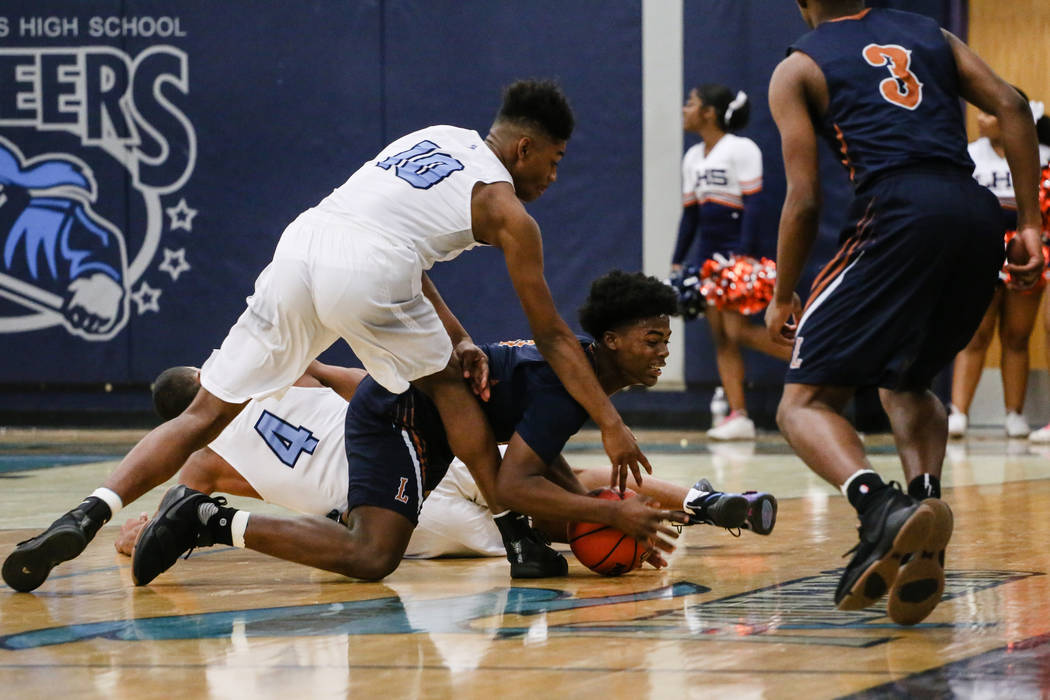 Legacyճ Cristian Pitts (3), center, jumps for the ball as Canyon SpringsՠChristopher Ward (10), left, follows during the second quarter of a basketball game at Canyon Springs High Scho ...