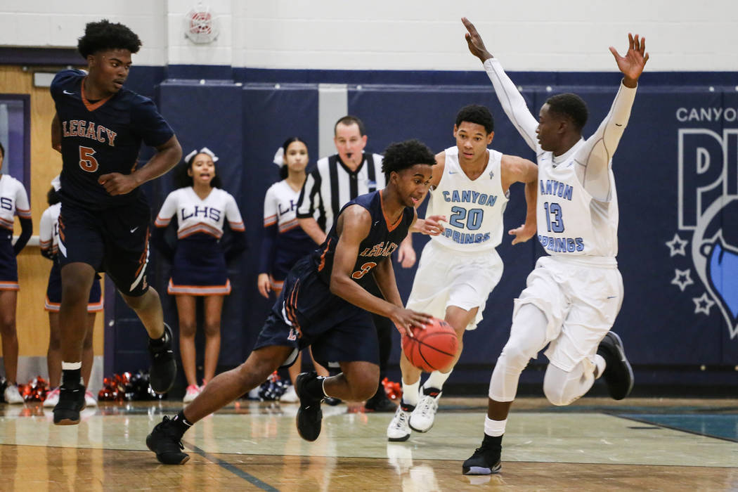 Legacyճ Chris White (5), left, watches as teammate Cristian Pitts (3), second from left, dribbles the ball past Canyon SpringsՠKaeJon Barnes (20), second from right, and Knylen Miller- ...