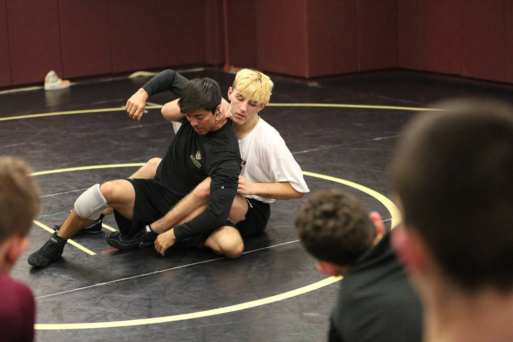 Coach Rayes Gonzales, left, uses Connor Bourne to illustrate how to escape a hold during wrestling practice at Faith Lutheran High School on Tuesday, Dec. 12, 2017. Michael Quine/Las Vegas Review- ...