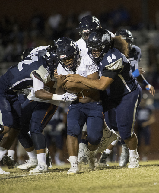 Samuel Turner (22) runs the ball through Shadow Ridge defenders Aubrey Nellems (22) and Jayden Roberts (84) during a Legacy High School Shadow Ridge High School game at Legacy High School in North ...