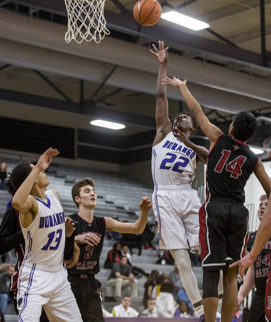 Durango's Vernell Watts (22) attempts a layup while Anthony Swift (13) watches and Desert Oasis defenders Nate Van (14) and Cade Savell (3) attempt to block him at Durango High School on Thursday, ...