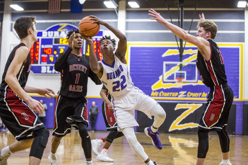 Durango's Vernell Watts (22) looks for a shot against the defense of Desert Oasis' Cade Savell (3) left, Felix Reeves, 1, and Jacob Heese (15) right, at Durango High School on Thursday, Jan. 18, 2 ...