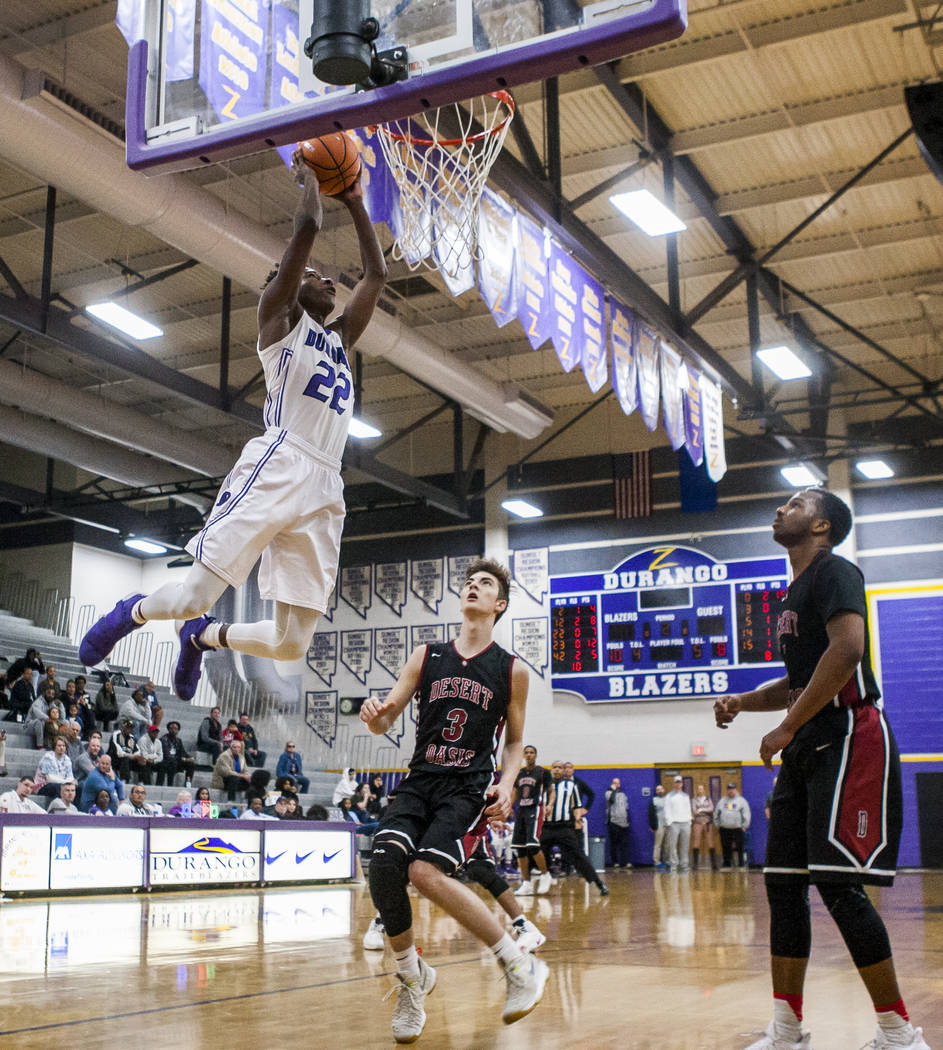 Durango's Vernell Watts (22) dunks while Desert Oasis' Cade Savell (3) and Manny Mitchell, 5, watch at Durango High School on Thursday, Jan. 18, 2018. Desert Oasis won 98-80.  Patrick Connolly Las ...