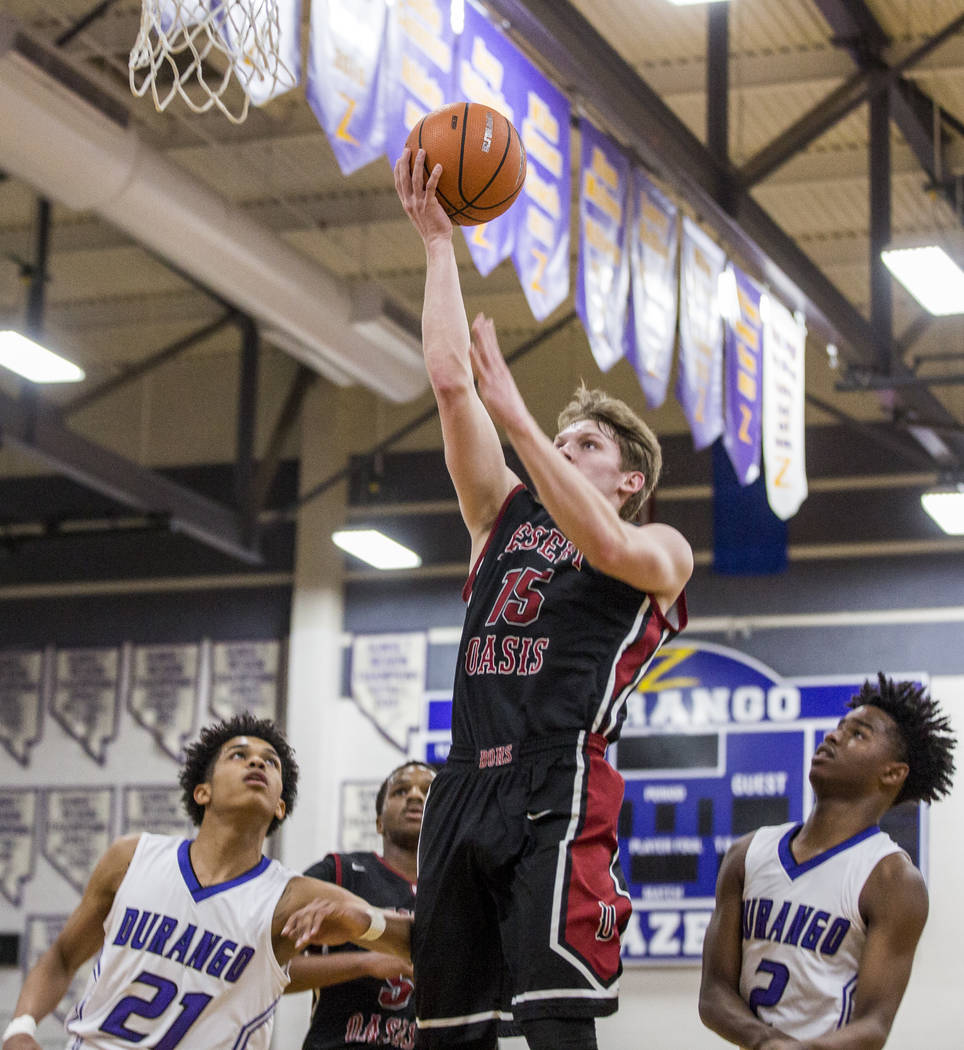 Desert Oasis' Jacob Heese (15) attempts a layup while Durango's Anthony Hunter (21) and Drake Booker, (2) watch at Durango High School on Thursday, Jan. 18, 2018. Desert Oasis won 98-80.  Patrick  ...