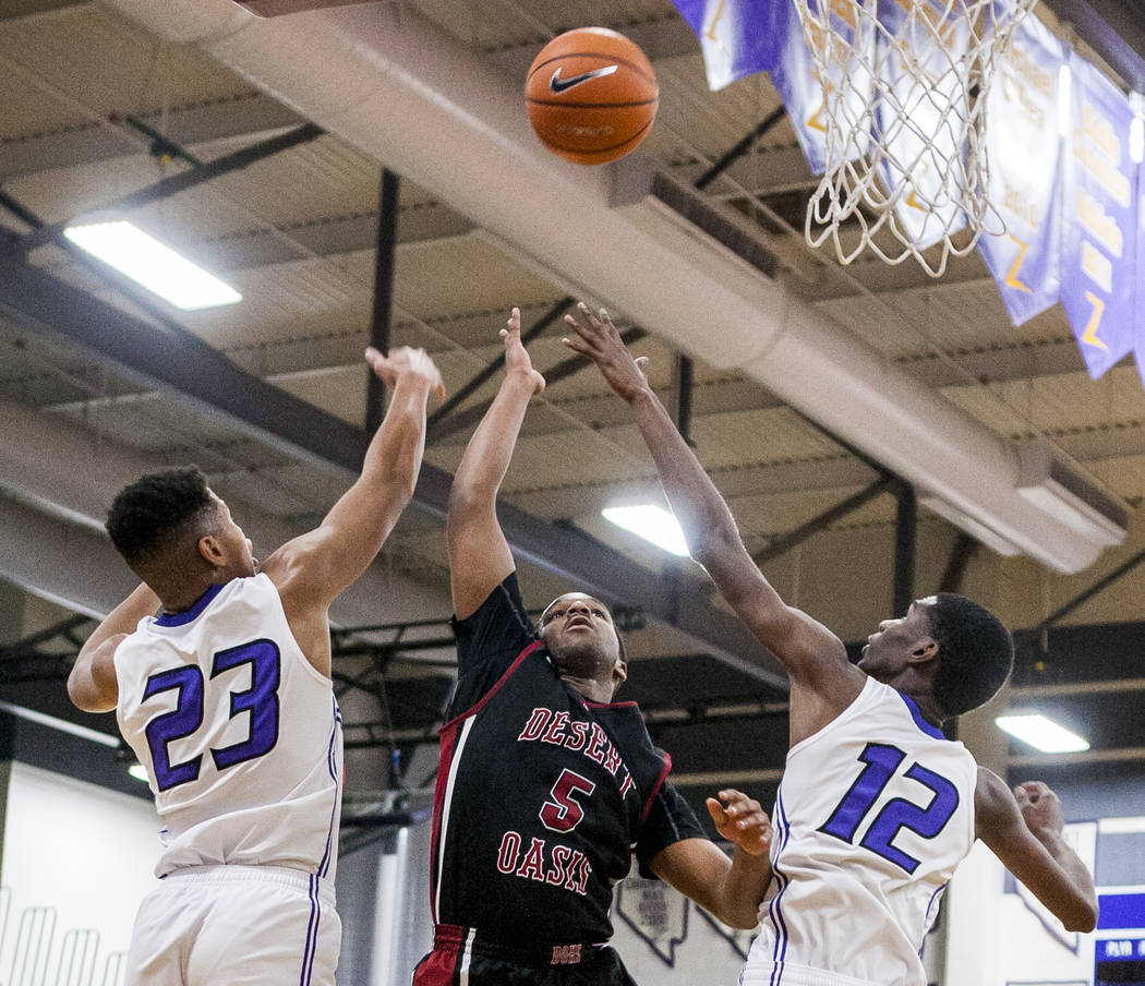 Desert Oasis' Manny Mitchell (5) reaches for the ball along with Durango's Nicquel Blake (23) and Leandre McIntyre (12) at Durango High School on Thursday, Jan. 18, 2018. Desert Oasis won 98-80.   ...