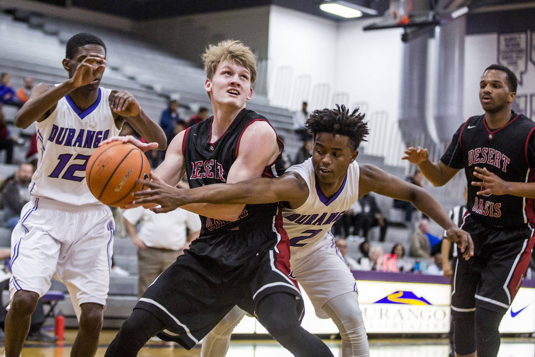 Desert Oasis' Jacob Heese (15) looks for a shot as Durango's Drake Booker (2) tries to grab it away while Manny Mitchell (5) and Durango's Leandre McIntyre (12) watch at Durango High School on Thu ...