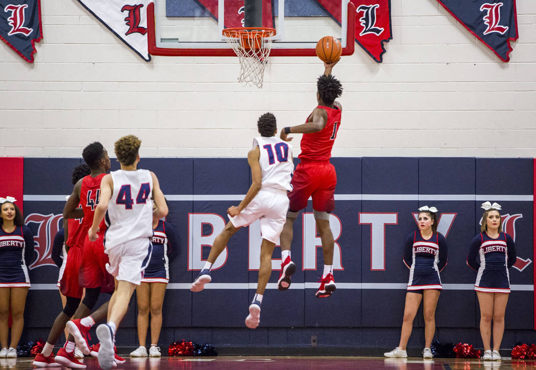 Coronado's Jaden Hardy (1) lays up while Liberty's Jordan Holt tries to block him and Liberty's Ray'mon Daniels (44) and Coronado's Taieem Comeaux (44) watch the action at Liberty High School on T ...