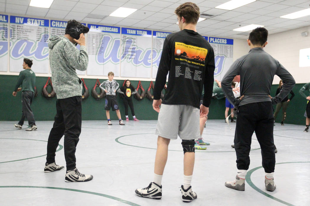 Green Valley High School junior wrestler Steele Dias, right, takes instruction with his training partner, 120-pound sophomore William Zernich, second from right, during practice at the school in H ...