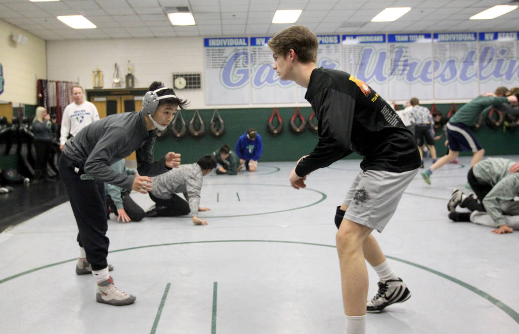 Green Valley High School junior wrestler Steele Dias, left, squares off with his training partner, 120-pound sophomore William Zernich, during practice at the school in Henderson Monday, Jan. 24,  ...