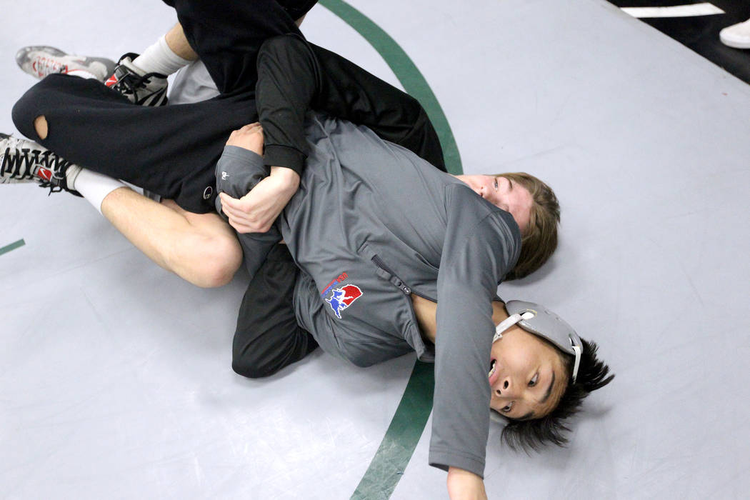 Green Valley High School junior wrestler Steele Dias, right, works on a move with his training partner, 120-pound sophomore William Zernich, during practice at the school in Henderson Monday, Jan. ...