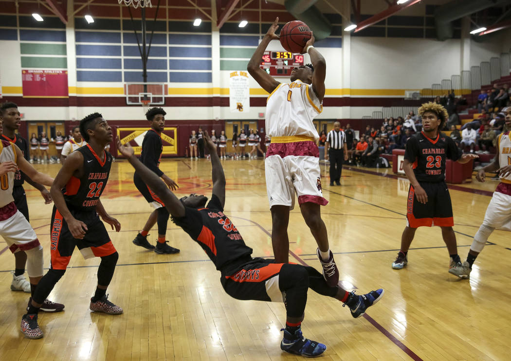Chaparral's Dejonte Allen (32) falls to the floors as Del Sol's Tyrell Hampton (0) looks for a shot during a varsity basketball game at Del Sol High School in Las Vegas, Friday, Jan. 26, 2018. Ric ...