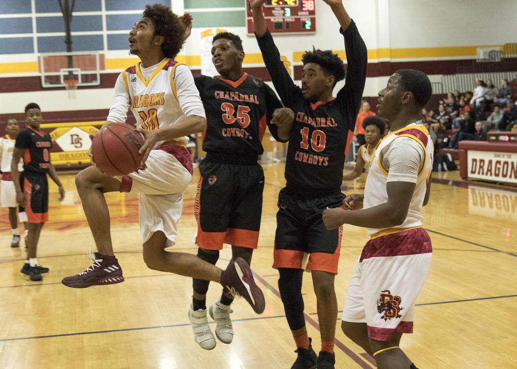 Del Sol's Devonte Anton Villarta (10) goes up for a shot against Chaparral's Meshach Hawkins (35) and Cairyn Bray (10) during a varsity basketball game at Del Sol High School in Las Vegas, Friday, ...