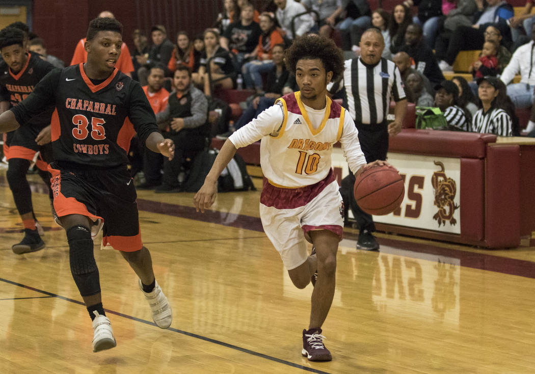 Del Sol's Devonte Anton Villarta (10) drives the ball as Chaparral's Meshach Hawkins (35) closes in during a varsity basketball game at Del Sol High School in Las Vegas, Friday, Jan. 26, 2018. Ric ...