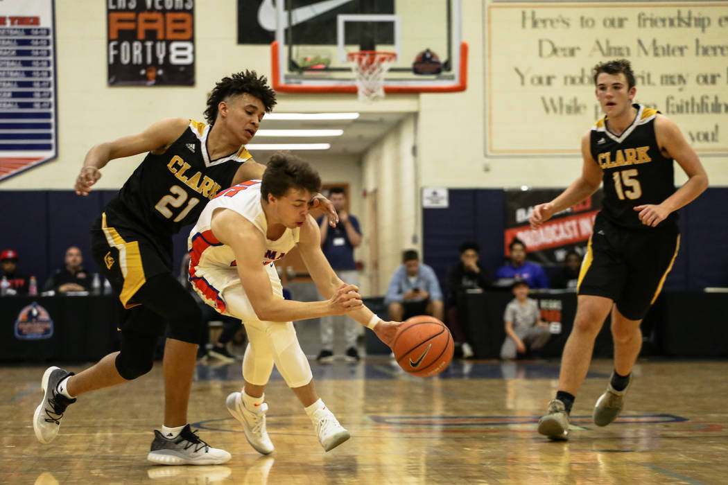 Clark Chargers' Jalen Hill (21) knocks the ball away from Bishop Gorman's Chance Michels (25) during the second half of the platinum division championship basketball game of the Tarkanian Classic  ...