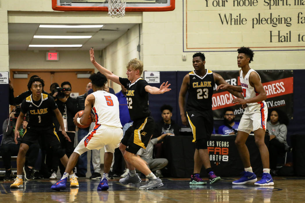 Bishop Gorman's Jamal Bey (5) is guarded by Clark Chargers' Trey Woodbury (22) during the first half of the platinum division championship basketball game of the Tarkanian Classic at Bishop Gorman ...