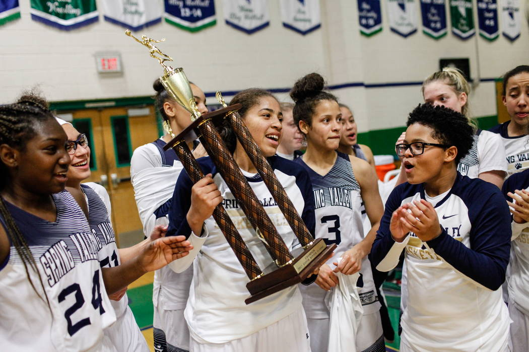 Spring Valley's Kayla Harris (11) holds the championship trophy after defeating Liberty 67-65 in the diamond bracket final of the Gator Winter Classic at Green Valley High School in Henders ...