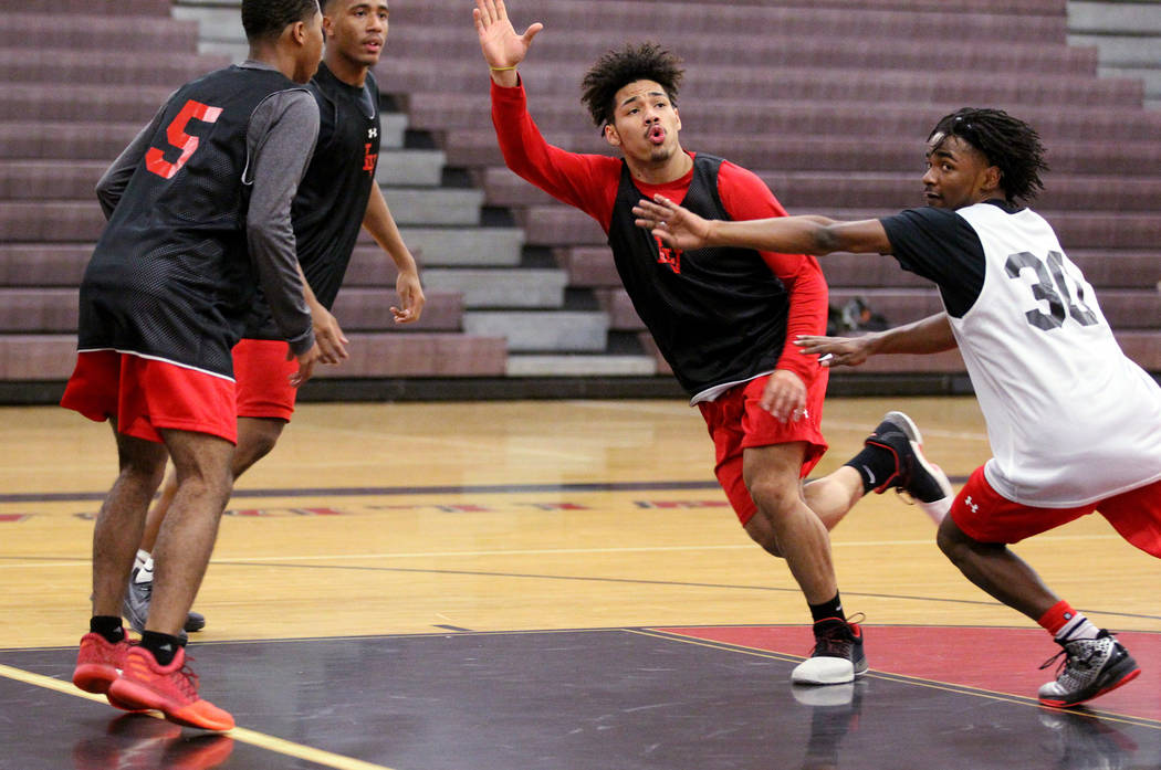 Las Vegas High School point guard Donovan Joyner, center, looks for a pass between Ronnie Moore (30), Marlon Harrison (5) and Zach Matlock during practice Monday, Jan. 8, 2018. The 5-foot-9 Joyner ...