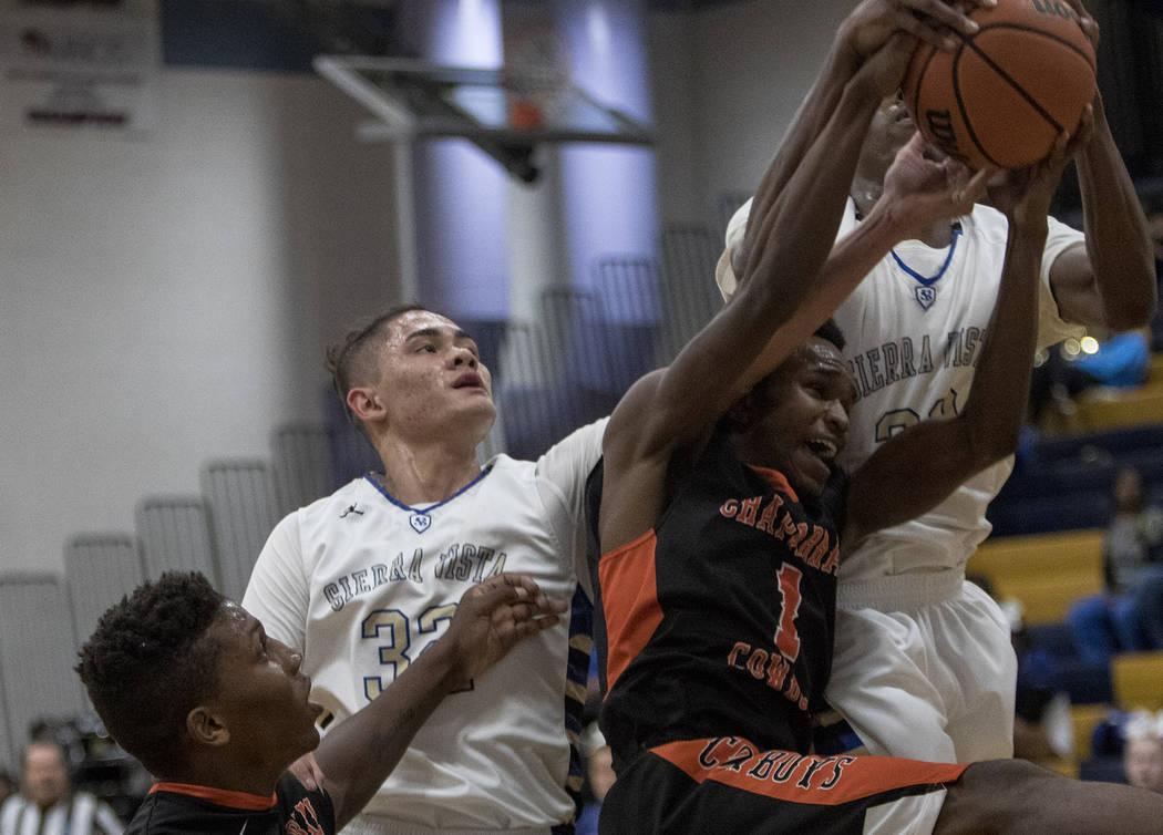 Sierra Vista High School's Maka Ellis (32) tries to capture the ball from Chaparral High School's Meshach Hawkins (35) and Tre Roberts (1) alongside teammate Jalen McFadden (33) at Sierra Vista Hi ...