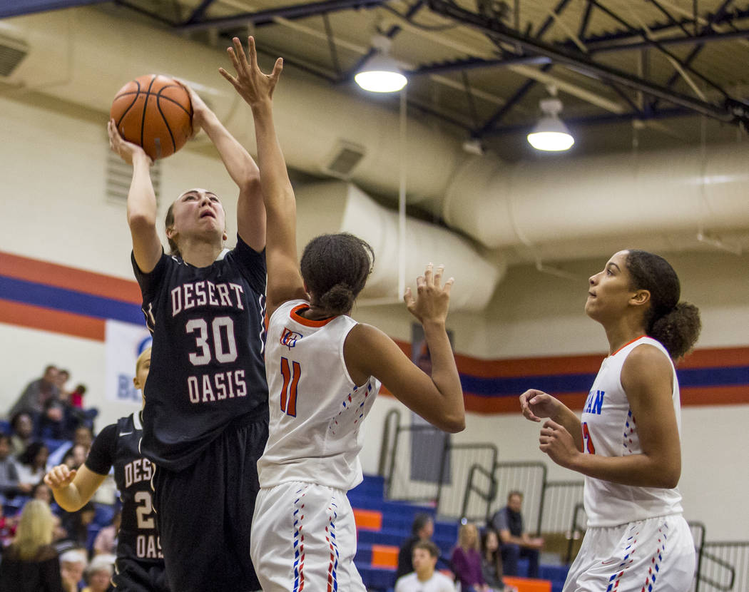 Desert Oasis' Sierra Mich'l looks for a shot while Bishop Gorman's Olivia Smith, center, attempts to block her at Bishop Gorman High School on Friday, Jan. 12, 2018. Desert Oasis won 69-61. Patric ...