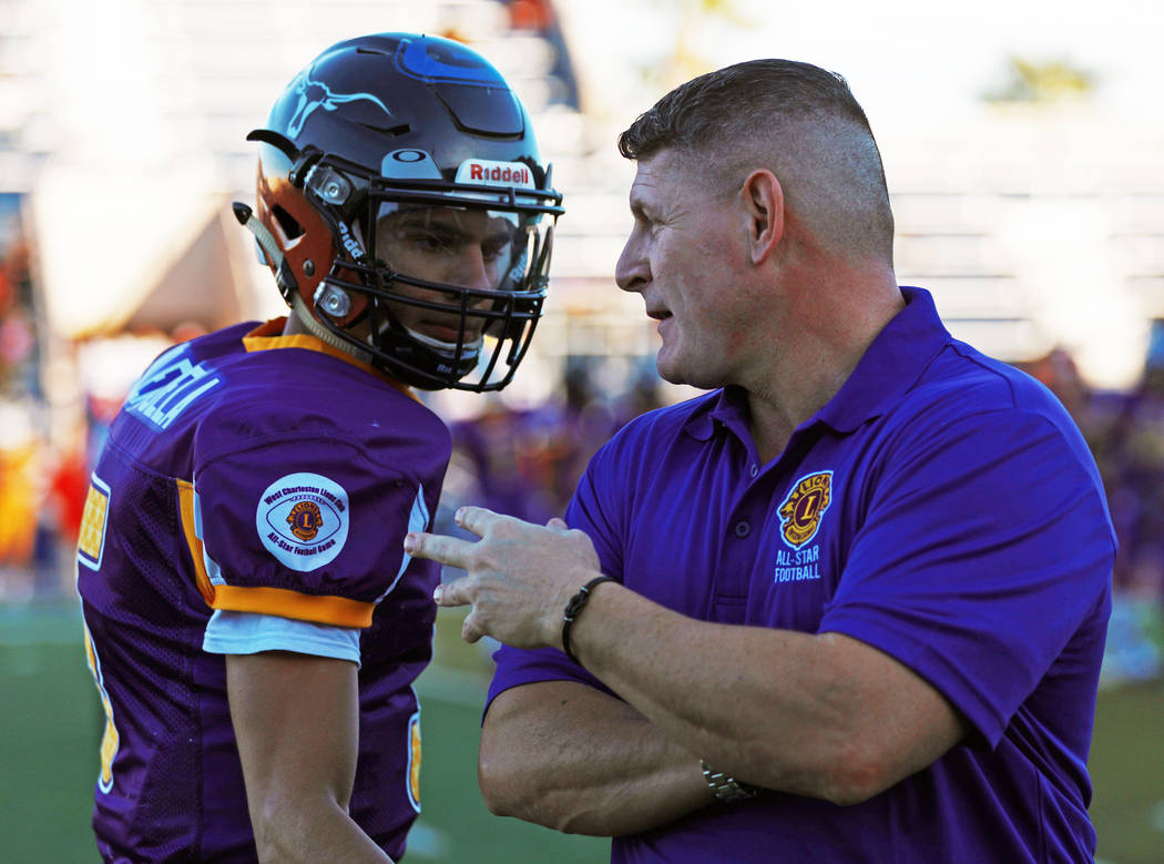 Sunset Head Coach John Isola, of Legacy High School, talks to quarterback Roberto Valenzuela, of Legacy High School, during the Lions All-Star football game at Bishop Gorman High School in Las Veg ...