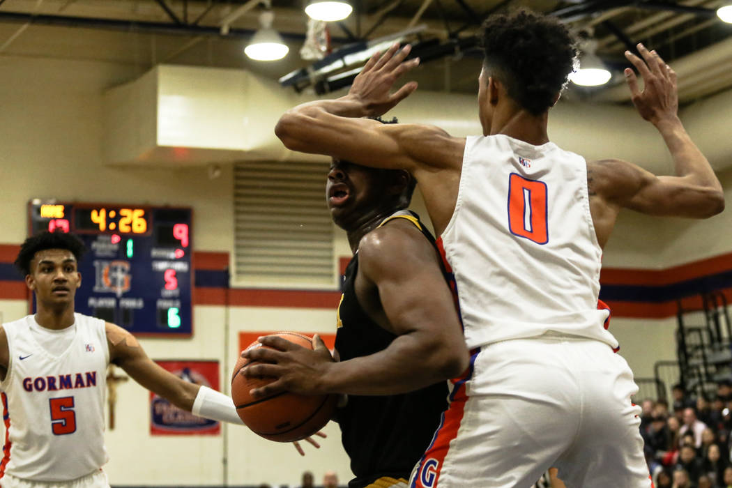 Clark Chargers' Antwon Jackson (23) is guarded by Bishop Gorman's Isaiah Cottrell (0) during the first half of the platinum division championship basketball game of the Tarkanian Classic at Bishop ...