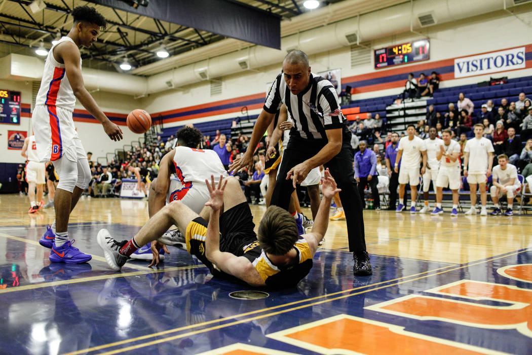 A referee calls a personal foul on Clark Chargers' Adam Forbes (24) after he fouled Bishop Gorman's Isaiah Cottrell (0) during the first half of the platinum division championship basketball game  ...