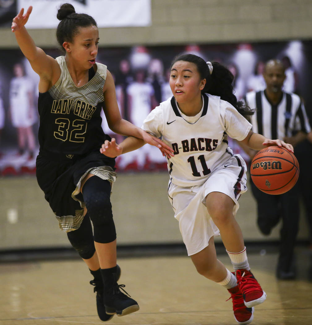 Desert Oasis' Kalena Halunajan (11) brings the ball up court against Spring Valley's Garrisen Freeman (32) during a basketball game at Desert Oasis High School in Las Vegas on Tuesday, Jan. 16, 20 ...