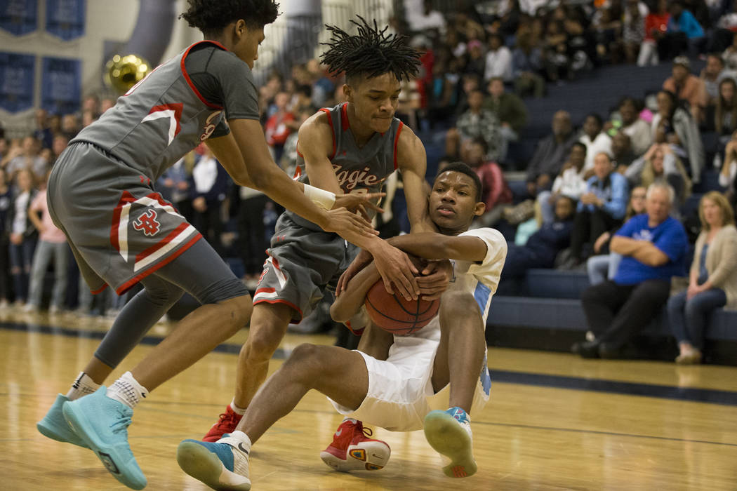 Centennial's Aaryn Anderson (12) holds the ball against pressure from Arbor View's Comillion Smith (20) in the basketball game at Centennial High School in Las Vegas, Wednesday, Jan. 17, 2018. Eri ...